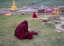 Moines tibétains s'asseyant sur la colline photo stock