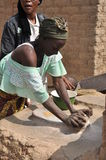 Moinho africano da grão da mulher com pedras imagens de stock