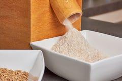 Moinho de farinha com farinha soletrada recentemente à terra imagens de stock