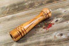 Moinho de pimenta de madeira na madeira rústica Fotografia de Stock