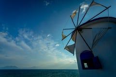 Moinho de vento branco grego tradicional na costa de mar no nascer do sol imagem de stock royalty free