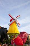 Moinho de vento colorido e descolagem vermelha dos balões de ar Fotos de Stock Royalty Free