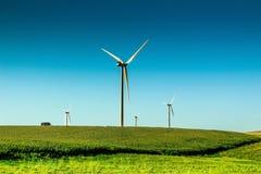 Moinho de vento das energias solares no campo do rolamento Imagens de Stock Royalty Free