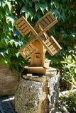 Moinho de vento de madeira em um tronco de árvore Fotografia de Stock