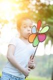 Moinho de vento de sopro da criança asiática fora fotos de stock