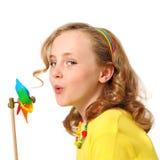 Moinho de vento de sopro da menina bonita fotos de stock royalty free