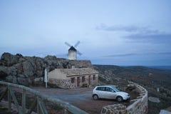 Moinho de vento e carro branco e sujo próximo de uma casa em Los Yebene fotos de stock