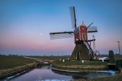 Moinho de vento holandês contra a sombra da terra fotografia de stock