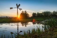 Moinho de vento mostrado em silhueta contra o ajuste Sun fotos de stock royalty free