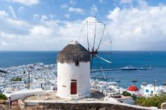 Moinho de vento na montanha pelo mar em Mykonos, Grécia Moinho de vento no seascape no céu nebuloso Construção branca com vela e  Imagem de Stock