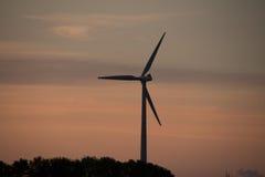 Moinho de vento no crepúsculo contra um céu do por do sol Imagem de Stock