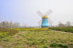 Moinho de vento no gramado florido na mola ensolarada Foto de Stock
