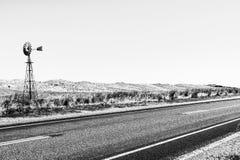 Moinho de vento perto da estrada asfaltada vazia com o interior australiano Austrália do norte imagens de stock royalty free