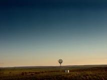 Moinho de vento que aumenta acima do deserto Fotografia de Stock Royalty Free