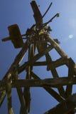 Moinho de vento velho mostrado em silhueta contra o céu azul Fotos de Stock Royalty Free