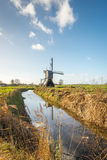 Moinho holandês do po'lder na extremidade de um córrego Imagens de Stock