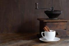 Moinho para o café com um copo e uma canela brancos fotografia de stock royalty free