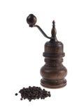 Moinho para a pimenta com os grãos de pimenta pretos isolados no bacground branco Imagem de Stock