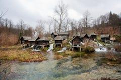 Moinhos de água de madeira construídos em um canal de fluxo rápido do rio Fotos de Stock Royalty Free