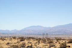 Moinhos de vento ao longo de uma paisagem do deserto Fotos de Stock Royalty Free