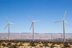 Moinhos de vento ao longo de uma paisagem do deserto Imagem de Stock Royalty Free