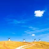 Moinhos de vento, campos verdes rurais, céu azul e nuvem pequena. Consuegra, Espanha imagens de stock