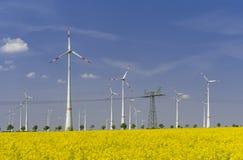 Moinhos de vento com campo e linha elétrica do canola fotografia de stock