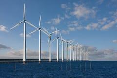 Moinhos de vento enormes que estão no mar imagens de stock royalty free