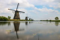Moinhos de vento holandeses históricos em um canal em Kinderdijk imagem de stock royalty free