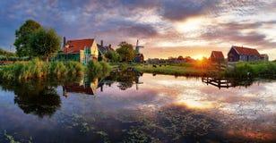 Moinhos de vento holandeses no por do sol, paisagem Imagem de Stock