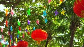 Moinhos de vento de papel coloridos e lanterna vermelha na floresta vídeos de arquivo
