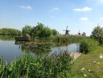 Moinhos de vento tradicionais, Kinderdijk, Holanda com o berço na frente dele fotos de stock