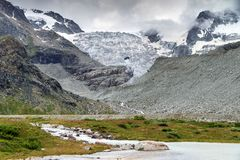 Moiry glacier in summer. Beautiful landscape at the Moiry glacier with melted ice pools and a ominous sky with clouds in summer in the Swiss pennine alps near stock photo