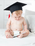 10 mois de bébé dans des couches-culottes utilisant le chapeau d'obtention du diplôme et employant t Images stock
