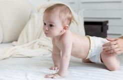 9 mois de bébé garçon dans des couches-culottes rampant sur le lit avec le shee blanc Photos libres de droits