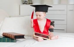 10 mois de bébé garçon dans le chapeau d'obtention du diplôme tenant le comprimé numérique Photos stock