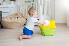 10 mois de bébé garçon essayant de se reposer sur le pot de chambre Images stock
