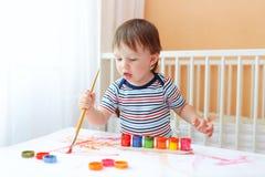 20 mois de bébé garçon peignant à la maison Images libres de droits