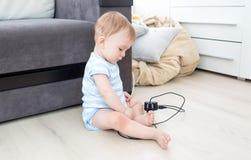 9 mois de bébé garçon s'asseyant sur le plancher au salon et jouant avec la prise et les fils électriques Images stock