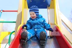 18 mois de bébé glissant sur le terrain de jeu en hiver Photo stock