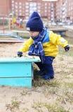 18 mois de bébé jouant avec le sable sur le terrain de jeu Image stock