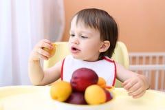 22 mois de bébé mangeant des pêches et des apricotes Photographie stock libre de droits