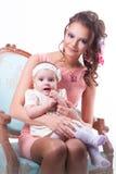 6 mois de bébé s'asseyant sur le recouvrement d'une mère et d'un kee joyeux Image libre de droits