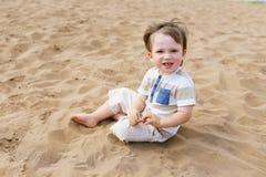 23 mois de garçon s'asseyant sur la plage de sable Photo stock