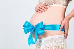 9 mois Le ventre est attaché avec un ruban bleu Fille enceinte attendant la naissance de son fils Image stock