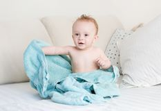 9 mois mignons de bébé garçon couvert en serviette bleue se reposant sur le lit après s'être baigné Photo stock