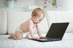 10 mois mignons de bébé garçon dans des couches-culottes se reposant sur le sofa et dactylographiant sur le clavier d'ordinateur  Photos stock