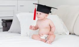 10 mois mignons de bébé garçon dans les dieapers utilisant le chapeau d'obtention du diplôme avec le tissel rouge Images libres de droits