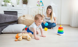 10 mois mignons de bébé jouant sur le plancher avec les jouets colorés Images stock