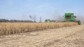 Moissonnant, rendement de rassemblement de machines agricoles du soja dans le domaine dans la saison de récolte contre le ciel bl banque de vidéos